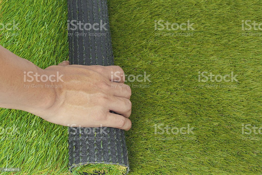 Artificial turf green grass roll with hand stock photo