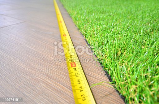 Artificial turf measuring indoors, copy space