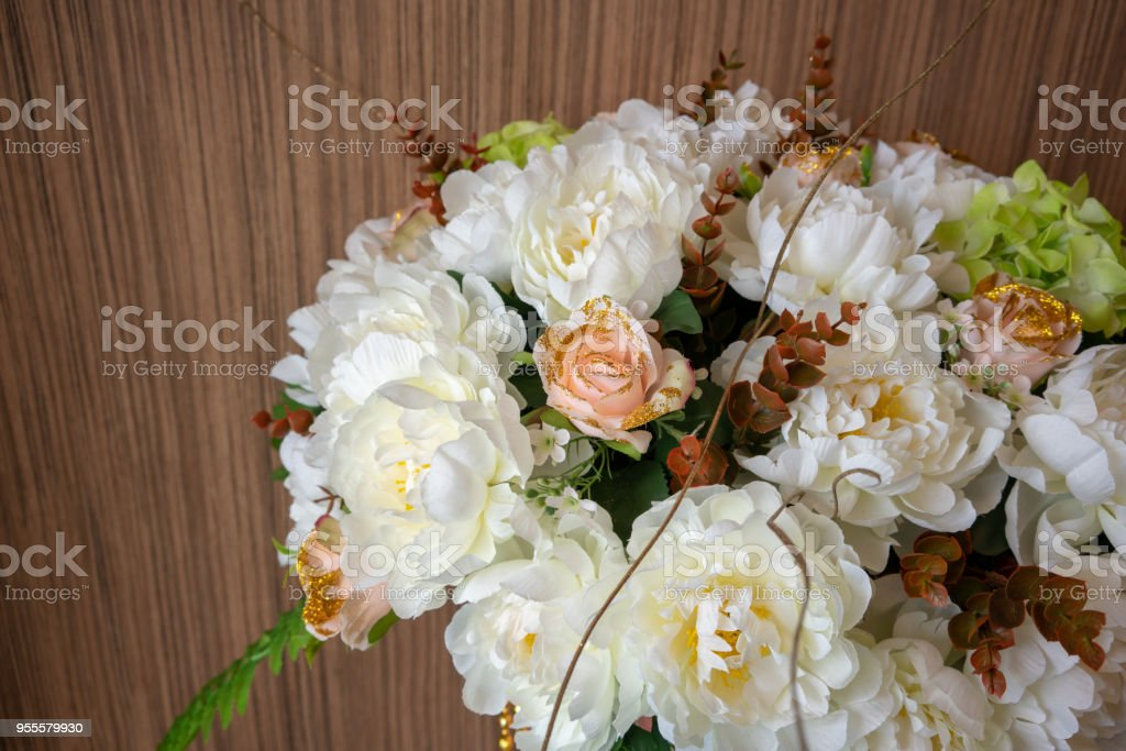 Artificial white flower on wooden background. Decorative handmade fabric flower for interior decoration stock photo