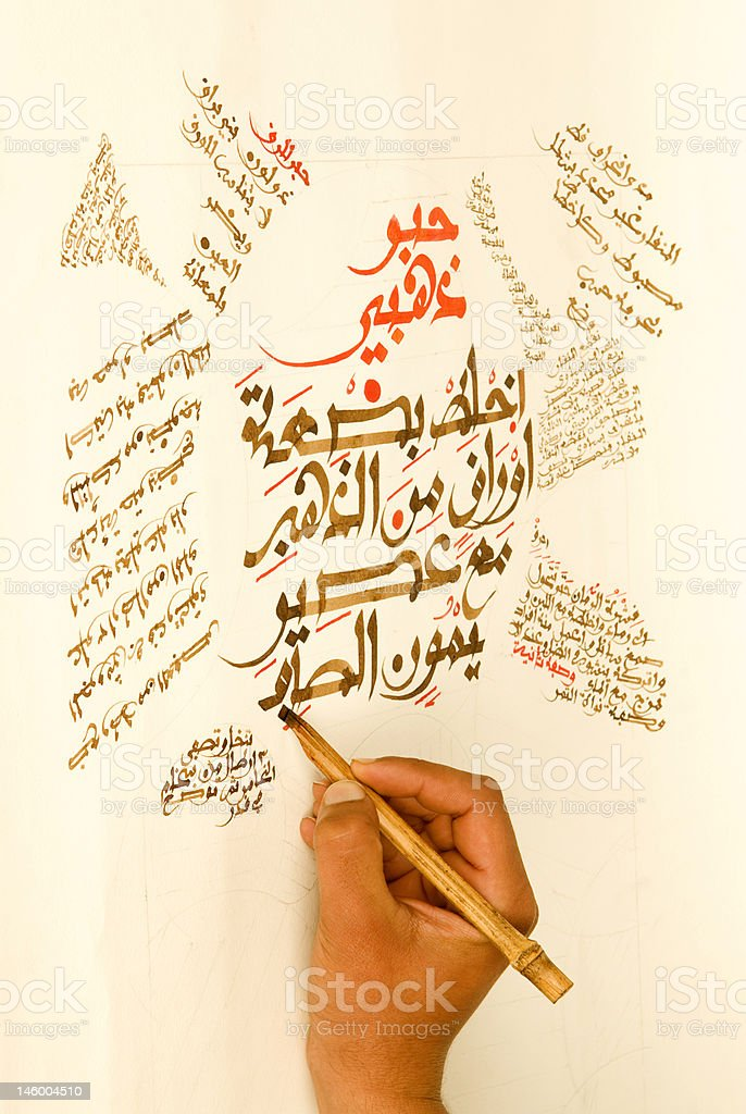 Artis writing Arabic Calligraphy characters on paper with pen stock photo
