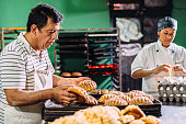 Baker sorting out Mexican sweet bread, known as Conchas, on trays for display