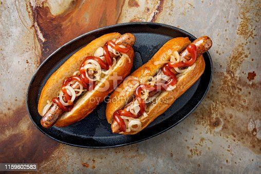 Overhead view of 2 artisan hot-dogs in a brioche bun with onions and pickles resting on a griddle pan. Colour, horizontal, some copy space against a rusty metal background.