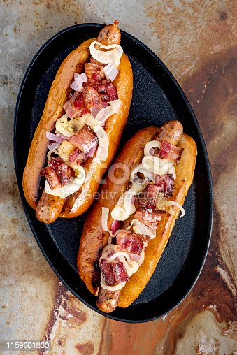 Overhead view of a selection of 2 artisan hot-dogs in a brioche bun with bacon and onion resting on a griddle pan. Colour, vertical, some copy space against a rusty metal background.