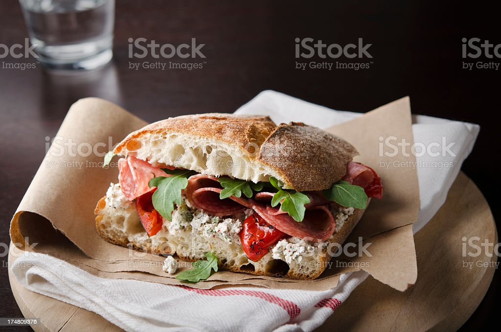 Artisan salami sandwich over a napkin in a round wood tray stock photo