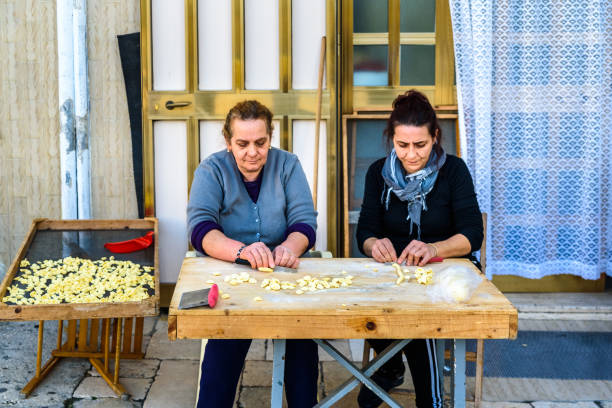 Artisan women preparing at the door of their house in the Italian city of Bari the traditional ear-shaped pasta, called orecchiette, made with flour and salt water, and folded in the street. Bari, Italy - March 8, 2019: Artisan women preparing at the door of their house in the Italian city of Bari the traditional ear-shaped pasta, called orecchiette, made with flour and salt water, and folded in the street. orecchiette stock pictures, royalty-free photos & images