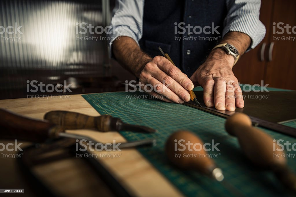 Artisan working with leather in a workshop  stock photo