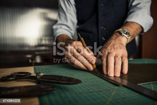 Close up shoot of an artisan working with leather in his laboratory.