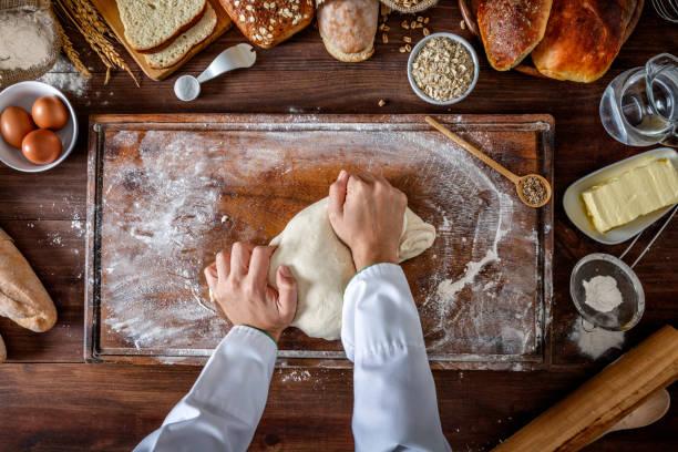 Boulangerie artisanale: artisan chef mains pétrissage de la pâte - Photo