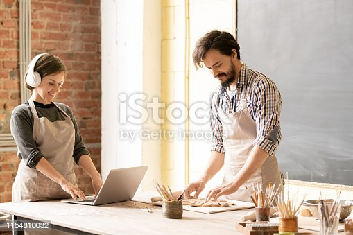 Young man in apron working over new clay item while his female colleague in headphones watching online video about earthenware design