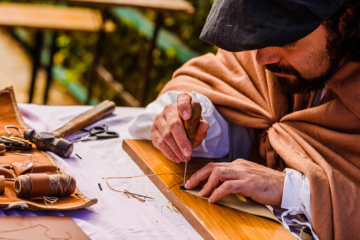 1130936245 istock photo Artisans disguised in medieval times showing old crafts in an exhibition of a festival. 1130936205