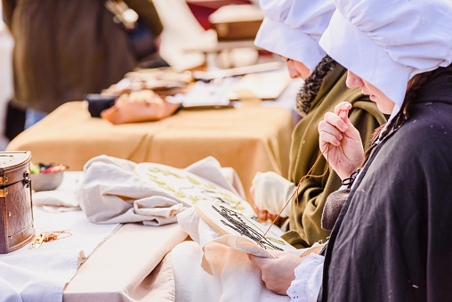 1130936245 istock photo Artisans disguised in medieval times showing old crafts in an exhibition of a festival. 1130936223
