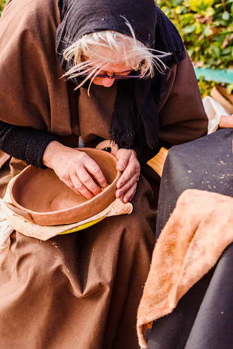 1130936245 istock photo Artisans disguised in medieval times showing old crafts in an exhibition of a festival. 1130936245