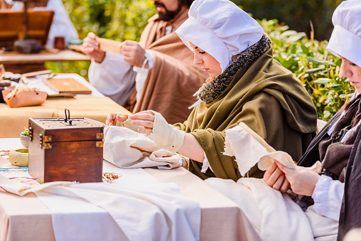 1130936245 istock photo Artisans disguised in medieval times showing old crafts in an exhibition of a festival. 1130936262