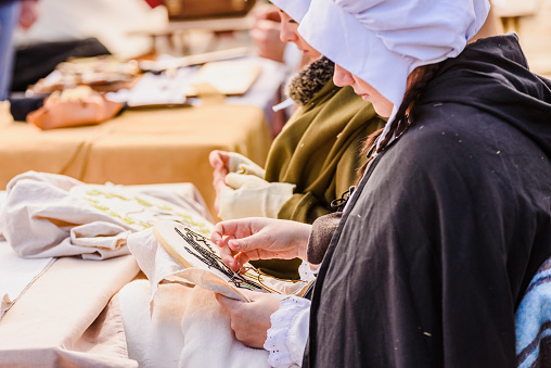 istock Artisans disguised in medieval times showing old crafts in an exhibition of a festival. 1130936281