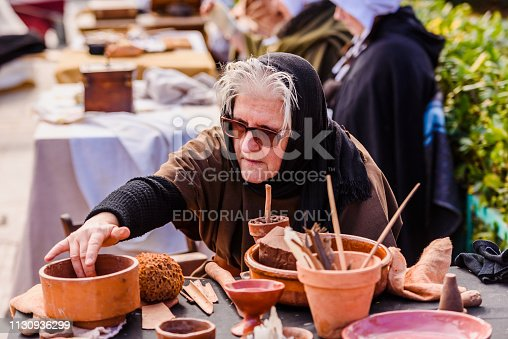 istock Artisans disguised in medieval times showing old crafts in an exhibition of a festival. 1130936299