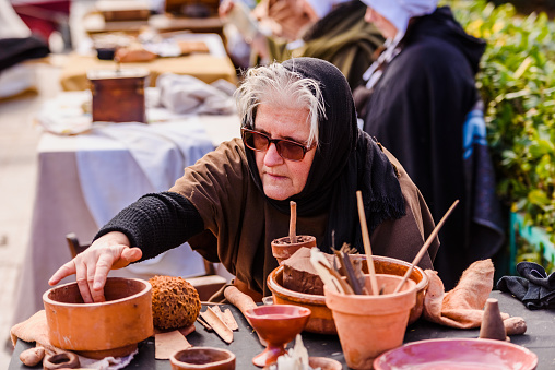 1130936245 istock photo Artisans disguised in medieval times showing old crafts in an exhibition of a festival. 1130936299