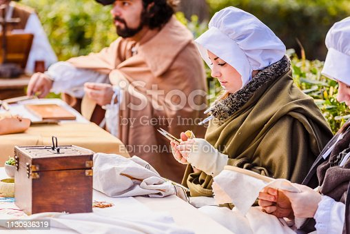 istock Artisans disguised in medieval times showing old crafts in an exhibition of a festival. 1130936319