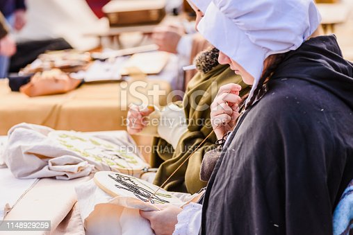 1130936245istockphoto Artisans disguised in medieval times showing old crafts in an exhibition of a festival. 1148929259