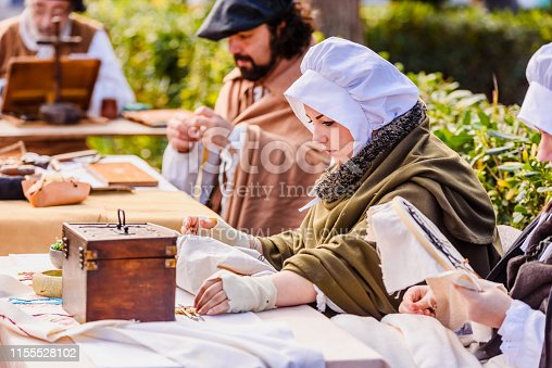 1130936245istockphoto Artisans disguised in medieval times showing old crafts in an exhibition of a festival. 1155528102