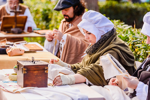 1130936245 istock photo Artisans disguised in medieval times showing old crafts in an exhibition of a festival. 1155528102