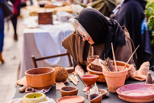 1130936245 istock photo Artisans disguised in medieval times showing old crafts in an exhibition of a festival. 1197845193