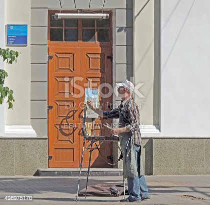 Voronezh, Russia - May 23, 2015: Spectacled mature men paint on the easel in the street sidewalk near building's front door