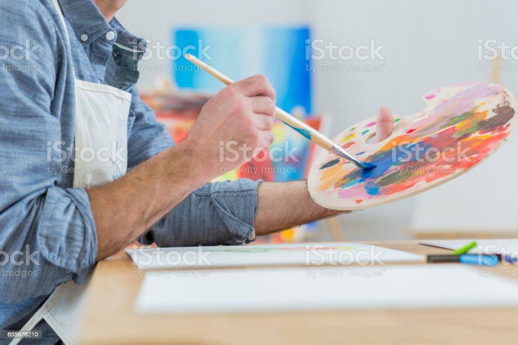 Artist blends paint on an artist's palette stock photo