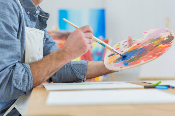 Artist blends paint on an artist's palette Man carefully blends paint on an artist's palette. His painting is on the table in front of him. View is from the neck down. alternative therapy stock pictures, royalty-free photos & images