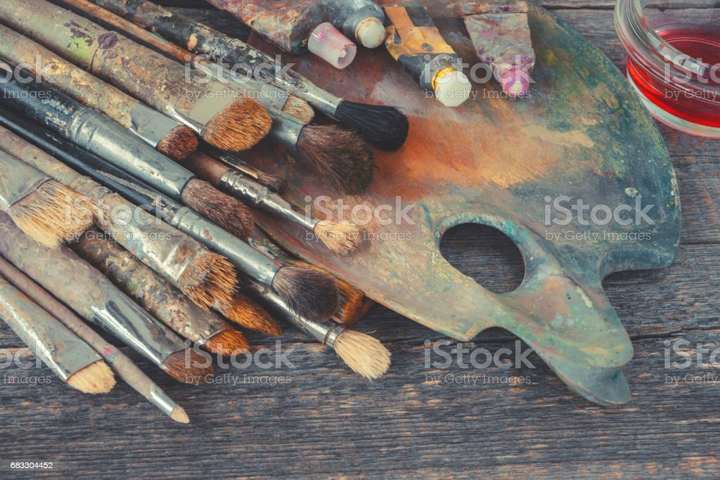 Artist brushes and tubes with paint on the palette stock photo