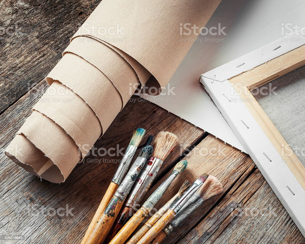 Artist canvas in roll, canvas stretcher and paintbrushes stock photo