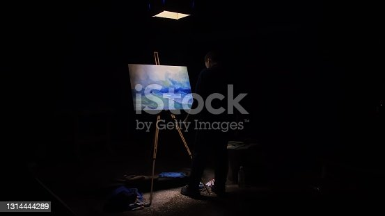 istock Artist copyist paint seascape with ship in ocean. Craftsman decorator draw as boat sail on blue sea. Black background. Wide angle shot. 1314444289