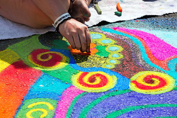 artist doing a bright chalk street painting - chalk drawing stock photos and pictures