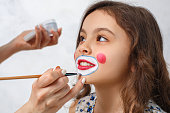 Artist paint clown face for a little kid isolated on white
