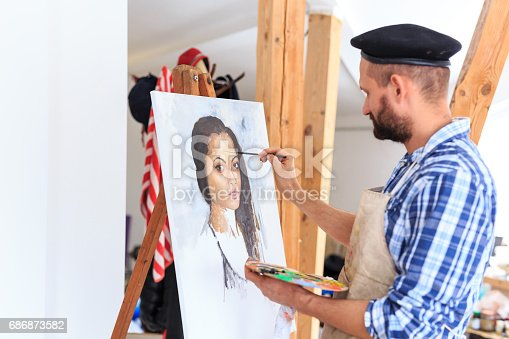 istock Artist drawing a portraiture of young woman 686873582