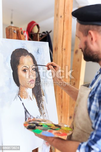 istock Artist drawing a portraiture of young woman 686873624