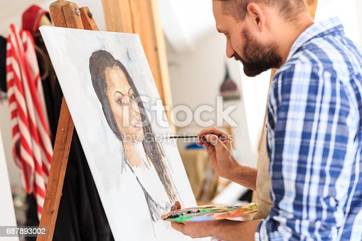 istock Artist drawing a portraiture of young woman 687893002
