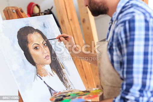 istock Artist drawing a portraiture of young woman 689215980