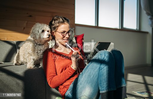 Female Artist Drawing At Home In Company Of Her Cute Poodle Dog