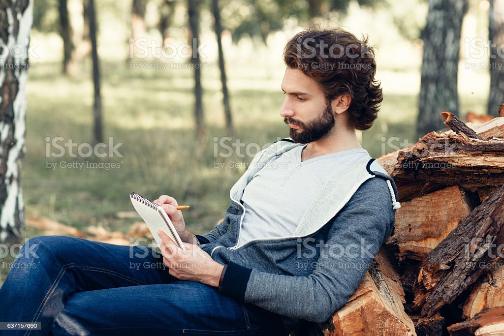 Artist drawing landscape in notebook, side view stock photo