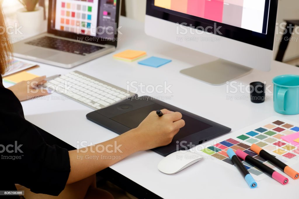 Artist drawing something on graphic tablet at the office. stock photo