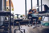 Artist drawning tattoo on man's leg in studio
