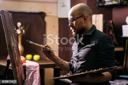 istock Artist draws a picture, holding a brush and palette 628873422