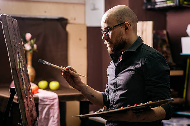 Artist draws a picture, holding a brush and palette stock photo