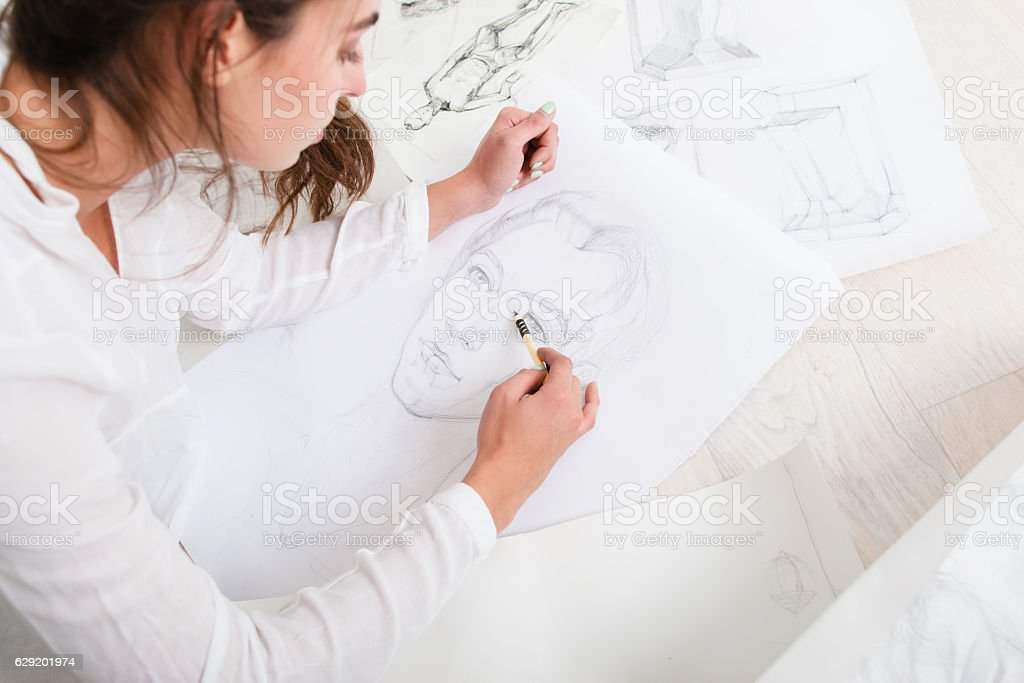 Artist finishing human pencil portrait on floor stock photo