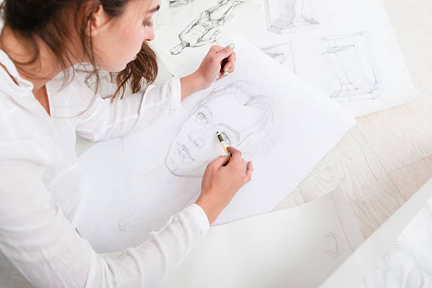 Artist finishing human pencil portrait on floor Artist finishing human pencil portrait on floor. top view on woman drawing sketch of female face. Art, craft, training, painting, inspiration concept illustrator stock pictures, royalty-free photos & images