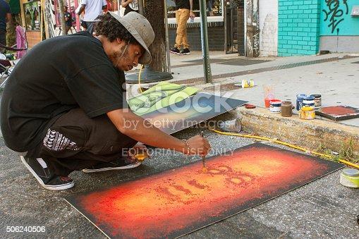 istock Artist Flicks Yellow Paint Onto Painting At Arts Festival 506240506