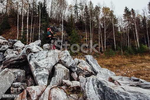 1062226450 istock photo artist girl painting sitting on the rocks at the cliff 639047414