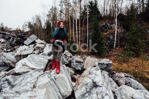 1062226450 istock photo artist girl painting sitting on the rocks at the cliff 639048206