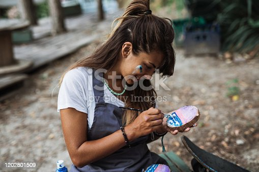 Beautiful and happy young woman enjoying in nature and summer camp. She siitting and painting in the woods.