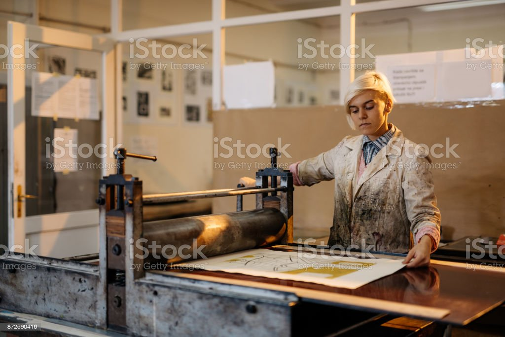Artist is producing artwork in her workshop with printing press and etching metal plate stock photo